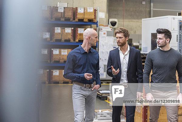 Drei Männer  die im Lagerraum der Fabrik laufen und reden.