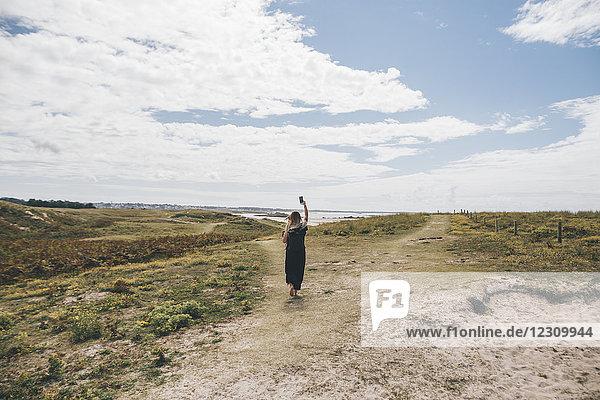 Frankreich  Bretagne  Landeda  Dunes de Sainte-Marguerite  junge Frau  die auf der Düne an der Küste mit Handy läuft