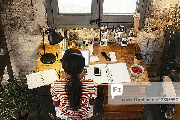 Rückansicht einer jungen Frau am Schreibtisch in einem Loft  die von oben gesehen am Laptop arbeitet.