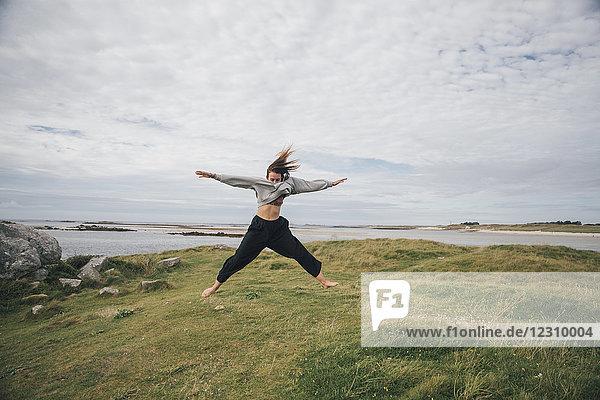 Frankreich  Bretagne  Landeda  Dunes de Sainte-Marguerite  junge Frau beim Springen an der Küste