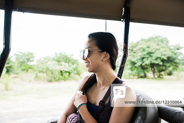 Young female tourist looking out bus on game drive trip  Botswana  Africa