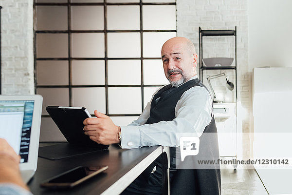 Porträt eines Geschäftsmannes mit digitalem Tablett  der in die Kamera schaut