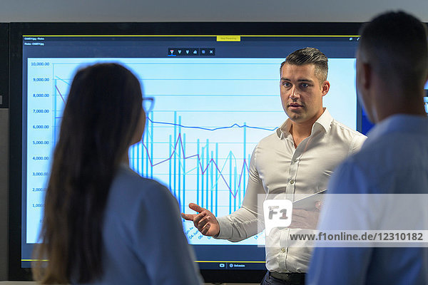 Man presenting business meeting with graph on screen