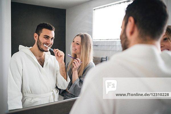 Mirror image of couple brushing teeth in bathroom