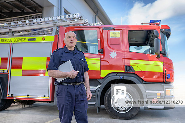 Portrait of fire chief in fire station with fire engine