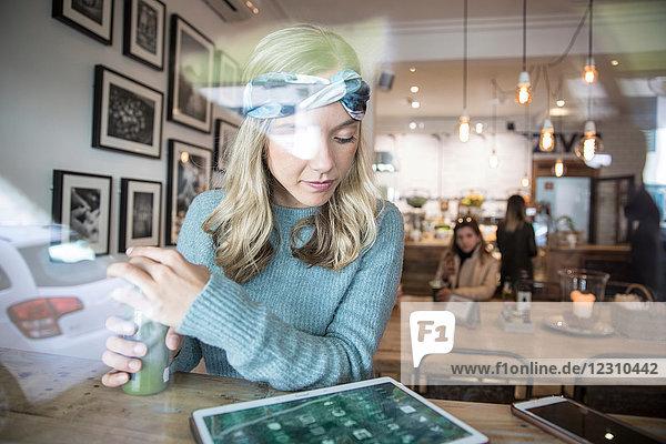 Junge Frau mit Gemüsesaft betrachtet digitales Tablett am Fensterplatz eines Cafés