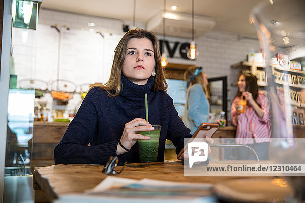 Young woman sitting in cafe  holding smartphone  drinking smoothie