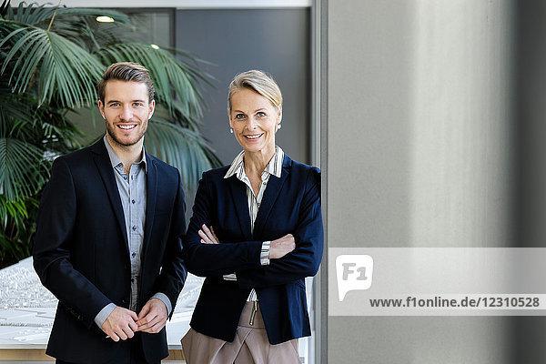 Geschäftsfrau und Mann im Bürokorridor  Porträt