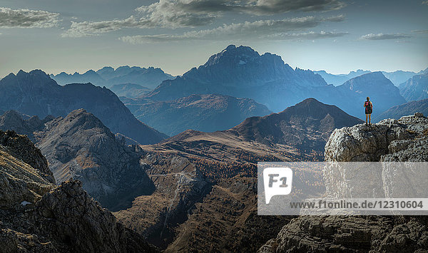 Climber on cliff looking at mountain ranges  Dolomites  Cortina d'Ampezzo  Veneto  Italy