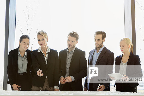 Businesswomen and men looking down at architectural model