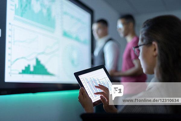 Geschäftsfrau sieht bei Geschäftsbesprechung Diagramme auf digitalem Tablet