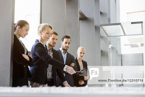 Geschäftsfrauen und -männer zeigen auf Architekturmodell im Büro
