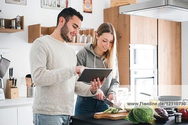 Ehepaar bereitet Essen mit digitaler Tablette zu
