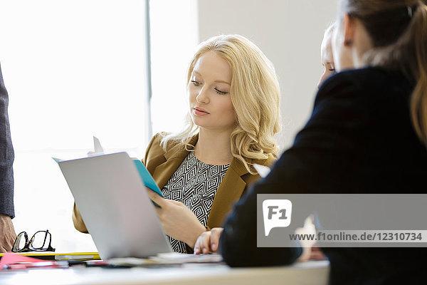 Junge Geschäftsfrauen in Bürobesprechung mit Blick auf Notizbuch