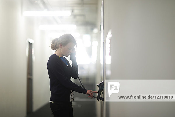 Woman using telephone in office