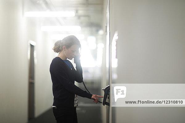 Frau benutzt Telefon im Büro