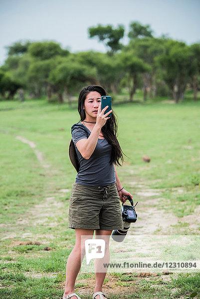 Junge Touristin fotografiert mit Smartphone und Kamera  Botswana  Afrika