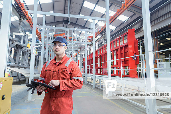 Portrait of worker with digital tablet in trailer factory