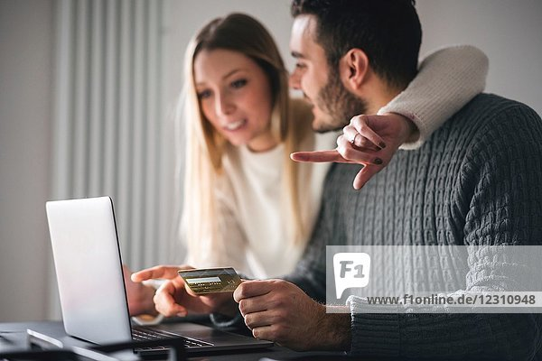 Couple with credit card using laptop