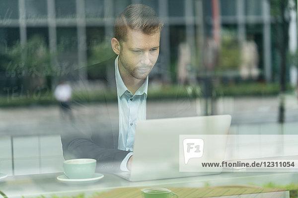 Geschäftsmann sitzt im Café  benutzt Laptop  durch Fenster gesehen