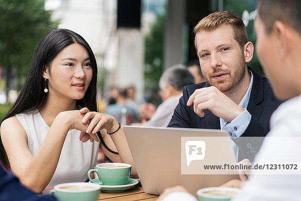 Gruppe von Geschäftsleuten  die sich im Café treffen  Laptop benutzen  im Freien