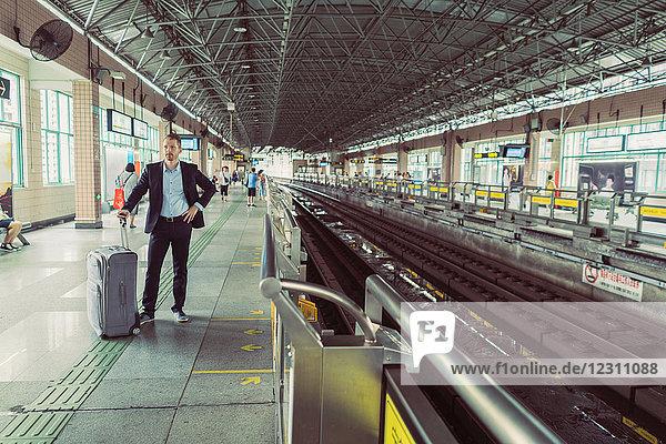 Geschäftsmann mit Rollkoffer  steht am Bahnhof und wartet auf den Zug