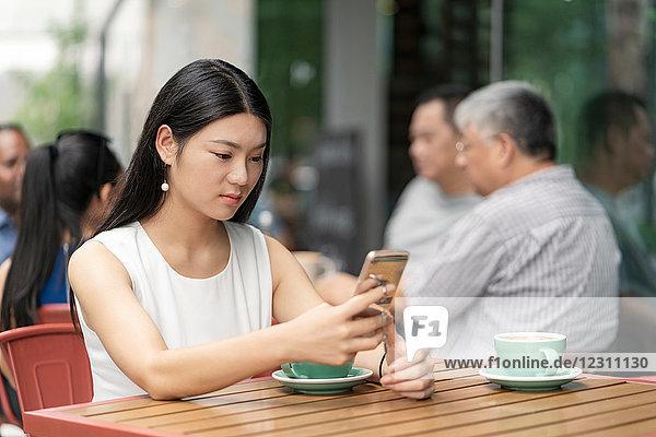 Geschäftsfrau sitzt im Freien  im Cafe  mit Smartphone