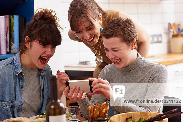 Friends laughing at something on mobile phone