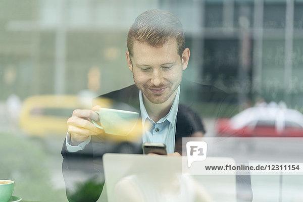 Geschäftsmann sitzt im Café  trinkt Kaffee  benutzt ein Smartphone  durchs Fenster gesehen