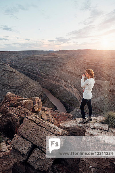 Young woman in remote setting  standing on rocks  looking at view  Mexican Hat  Utah  USA