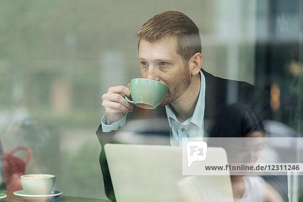 Geschäftsmann sitzt in Café  trinkt Kaffee  benutzt Laptop  durch Fenster gesehen