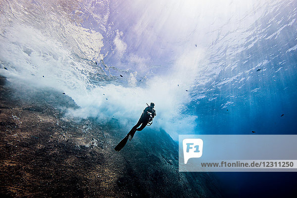 Underwater view of female diver exploring roca partida pinnacle  Socorro  Baja California  Mexico