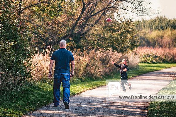 Vater und Sohn spielen auf dem Weg mit dem Ball