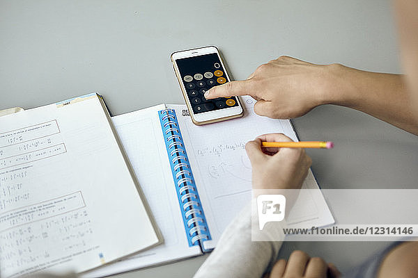 Students using smartphone calculator function while completing math assignment
