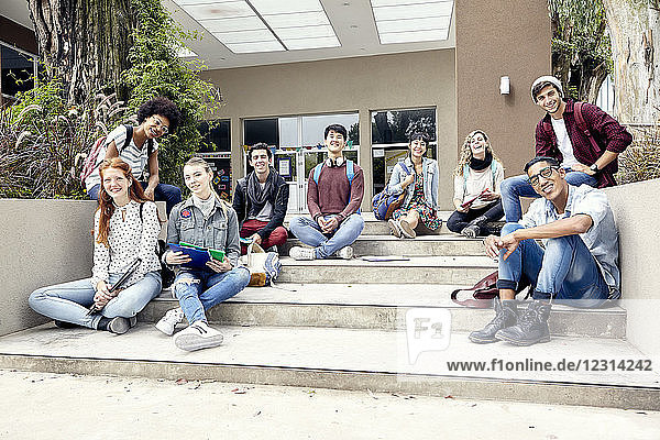 College students sitting on steps outside building  portrait