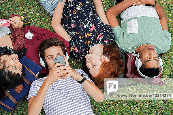 College friends relaxing on grass together