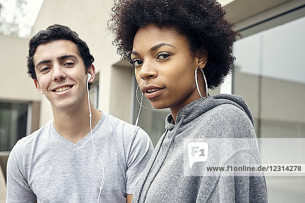 Friends listening to music together with earphones  portrait