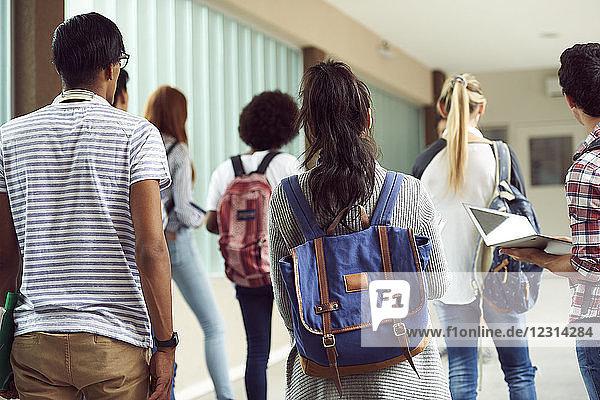 Students walking in school corridor  rear view
