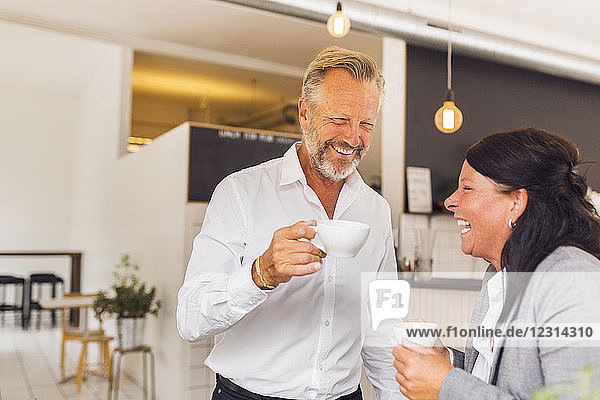 Senior man and mature woman laughing in cafe Senior man and mature woman laughing in cafe