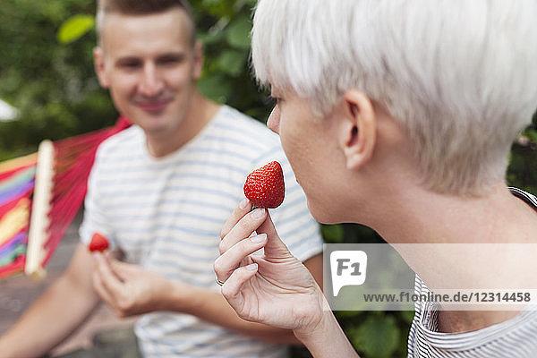Couple eating strawberries in garden Couple eating strawberries in garden