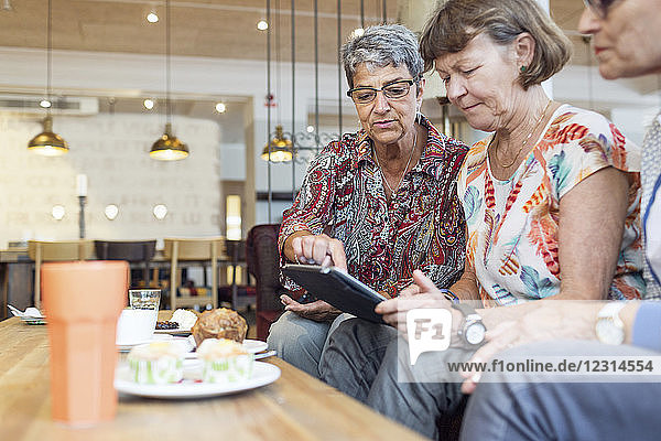Three women using digital tablet in cafe