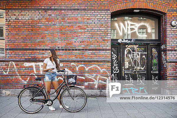 Teenage girl (14-15) standing on sidewalk with bicycle Teenage girl (14-15) standing on sidewalk with bicycle