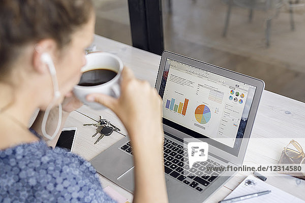 Woman drinking coffee and looking at charts in laptop