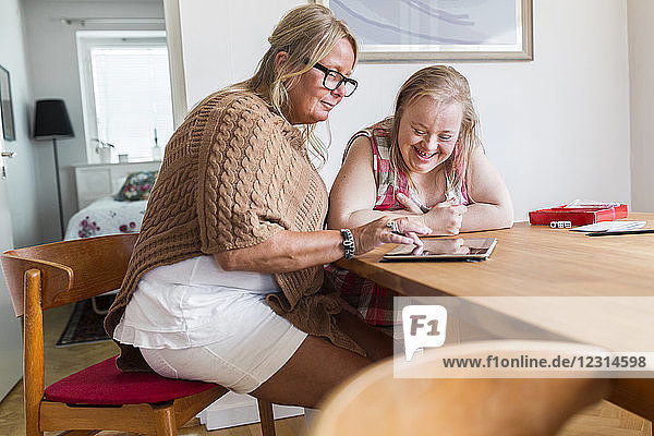 Mother and daughter with down syndrome using digital tablet