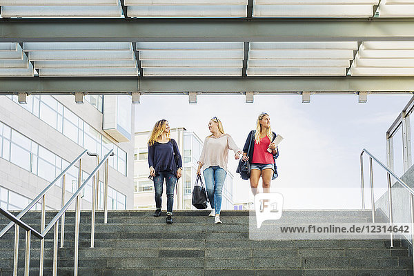 Three young women walking down stairs