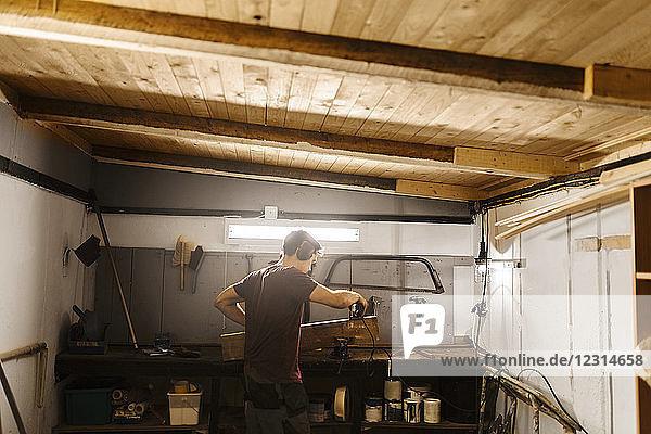 Man polishing wood in garage Man polishing wood in garage