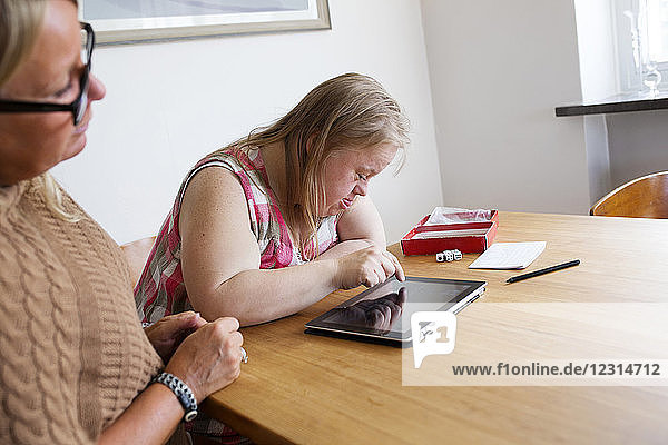 Daughter with down syndrome using digital tablet  mother looking