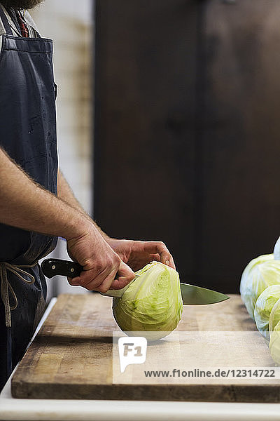 Mid section of man cutting cabbage