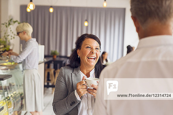 Senior man and mature woman laughing in cafe