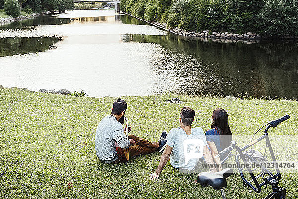 Three people relaxing in park with guitar
